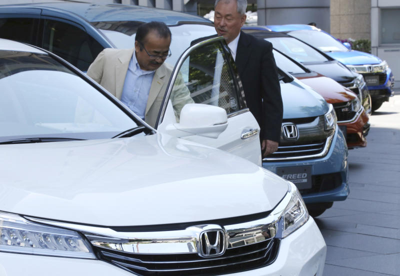Visitors examine a car displayed at the showroom at the Honda Motor Co. headquarters in Tokyo, Wednesday, May 8, 2019. Honda reported a loss for January-March, despite growing sales, as an unfavorable exchange rate, income tax expenses and other costs hurt results. (AP Photo/Koji Sasahara)