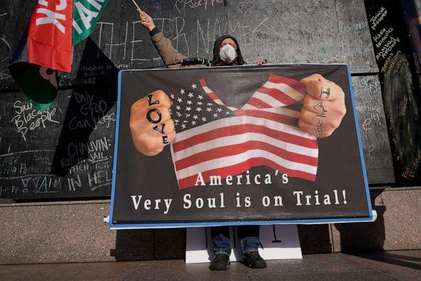 A protester holds a sign across the street from the Hennepin County Government Center, April 6, 2021,in Minneapolis where testimony continues in the trial of former Minneapolis police officer Derek Chauvin charged with murder in the death of George Floyd. (Jim Mone/AP)