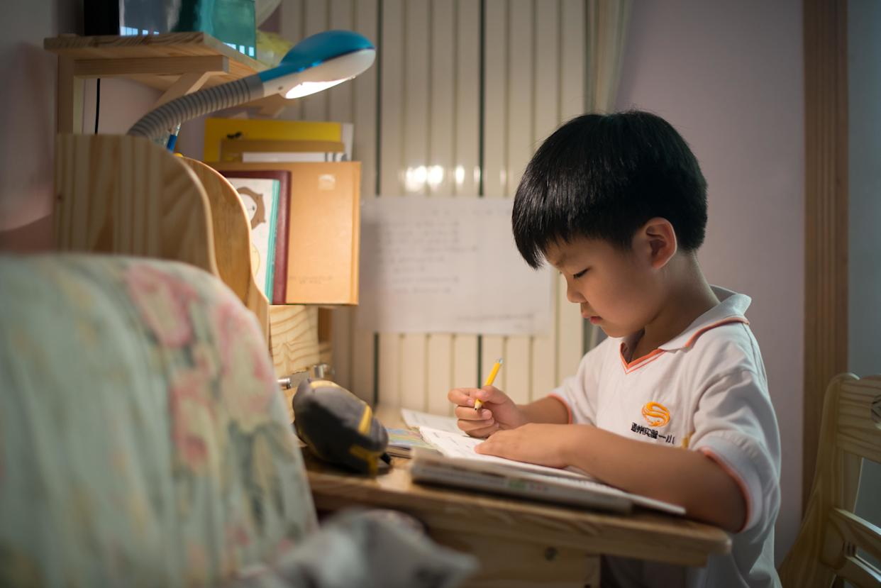 Wei Hanqi, 9, completes his homework at his home in Beijing on June 19, 2013.