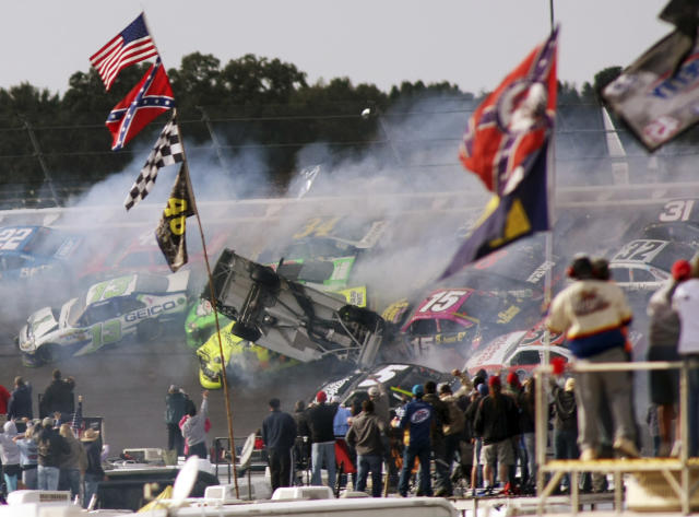 Tony Stewart (14) flips over as Clint Bowyer (15), Regan Smith (78), Jeff Burton (31), Jimmie Johnson (48), Casey Mears (13), Aric Almirola (43), Dale Earnhardt Jr., (88) and Sam Hornish Jr. (22) crash around him during the NASCAR Sprint Cup Series auto race at Talladega Superspeedway in Talladega, Ala., Sunday, Oct. 7, 2012. (AP Photo/Greg McWilliams)