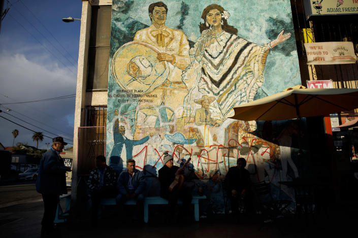 """Men sit outside a store in front of the mural """"El Corrido de Ricardo Valdez,"""" painted in 1994 by Juan Solis, in Mariachi Plaza in February in Boyle Heights, Los Angeles. (Photo: Patrick T. Fallon for Yahoo News)"""