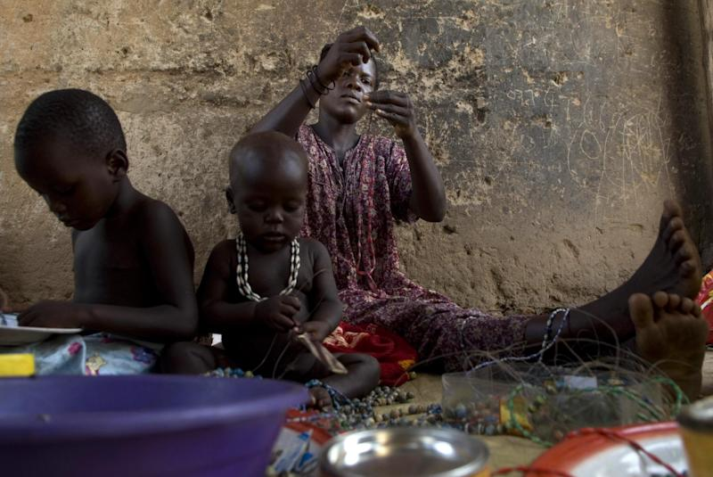 A Ugandan woman makes paper beads with the help of her children on March 1, 2008, at their home in the Namuwungo slum in Kampala