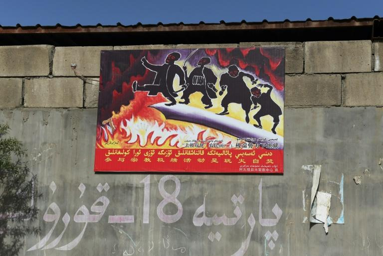 "A propaganda poster in China's Xinjiang reads ""Participating in extremist activities is playing with fire"""