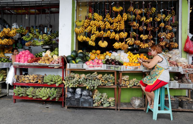 A vendor surfs internet on her mobile phone as she waits for customers at a fruit stall at in Paranaque, Metro Manila