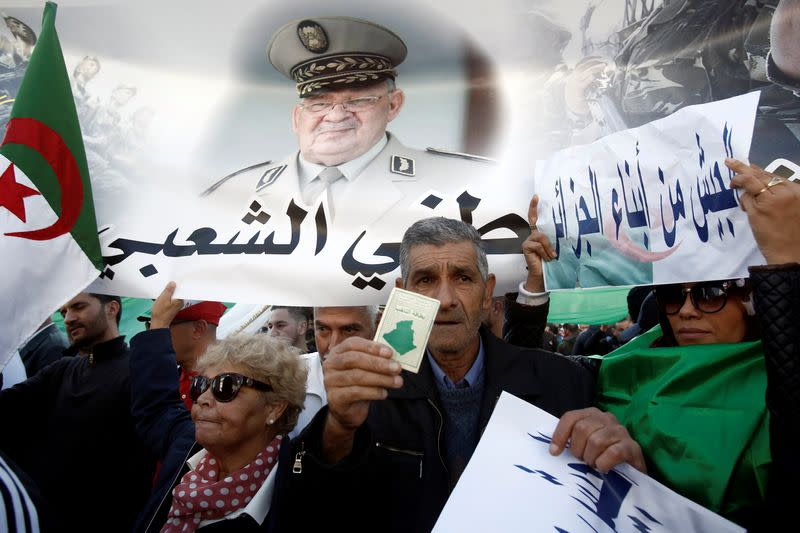 Pro-government supporters carry banners during a demonstration in Algiers