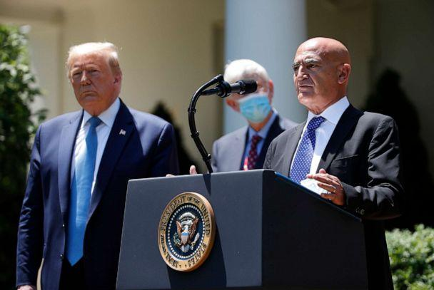 PHOTO: President Donald Trump, left, listens as Moncef Slaoui, a former GlaxoSmithKline executive, speaks about the coronavirus in the Rose Garden of the White House, May 15, 2020, in Washington. (Alex Brandon/AP)
