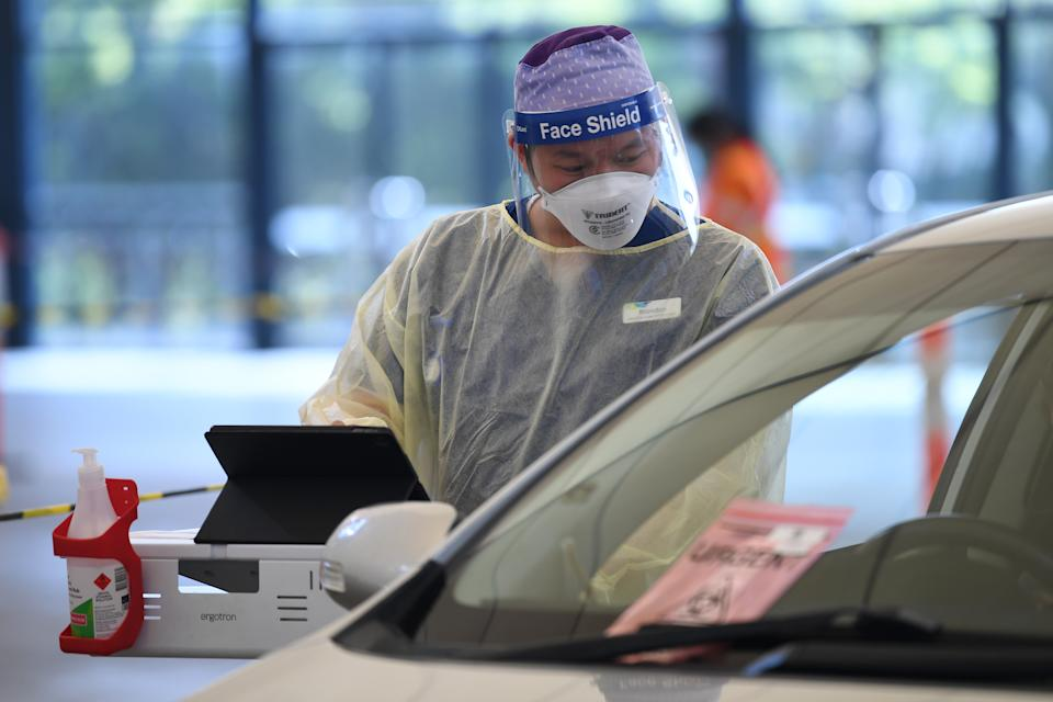 Helathcare worker Brandon Nguyen is seen working at a drive-through Covid19 testing facility in Melbourne, Friday, October 8, 2021. Source: AAP