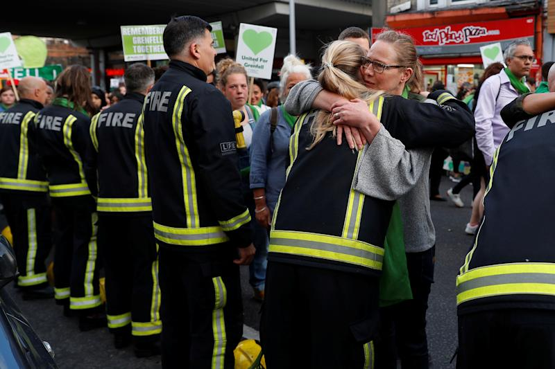A participant in a Silent March marking the first anniversary of the Grenfell Tower fire, hugs a firefighter as they walk near the tower in London, Britain June 14, 2018. REUTERS/Peter Nicholls