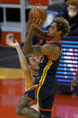 Golden State Warriors guard Kelly Oubre Jr., top, shoots over Minnesota Timberwolves forward Jake Layman during the first half of an NBA basketball game in San Francisco, Wednesday, Jan. 27, 2021. (AP Photo/Jeff Chiu)