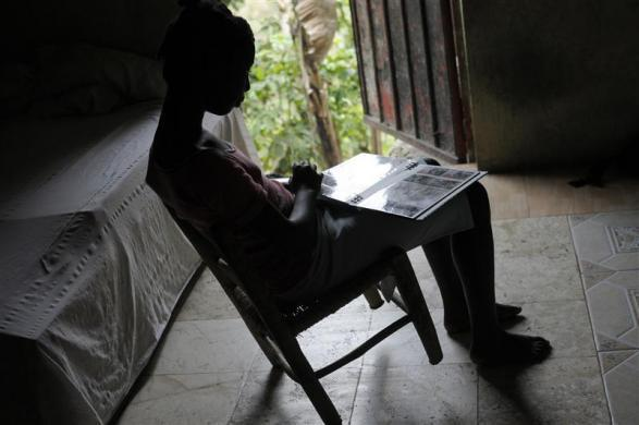 Haitian girl Fabien Destine, 14, who suffers from VSP congenital heart disease, or a hole in the chamber wall, looks through family photos at home in Port-au-Prince, March 24, 2012.