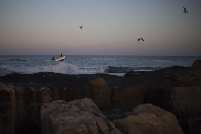 Fishermen on their boat return from a fishing trip on the Mediterranean Sea, in the Israeli Arab village of Jisr al-Zarqa, Israel, in the early morning of Thursday, Feb. 25, 2021. After weathering a year of the coronavirus pandemic, an oil spill in the Mediterranean whose culprits remain at large delivered another blow for the fishermen of Jisr al-Zarqa. (AP Photo/Ariel Schalit)