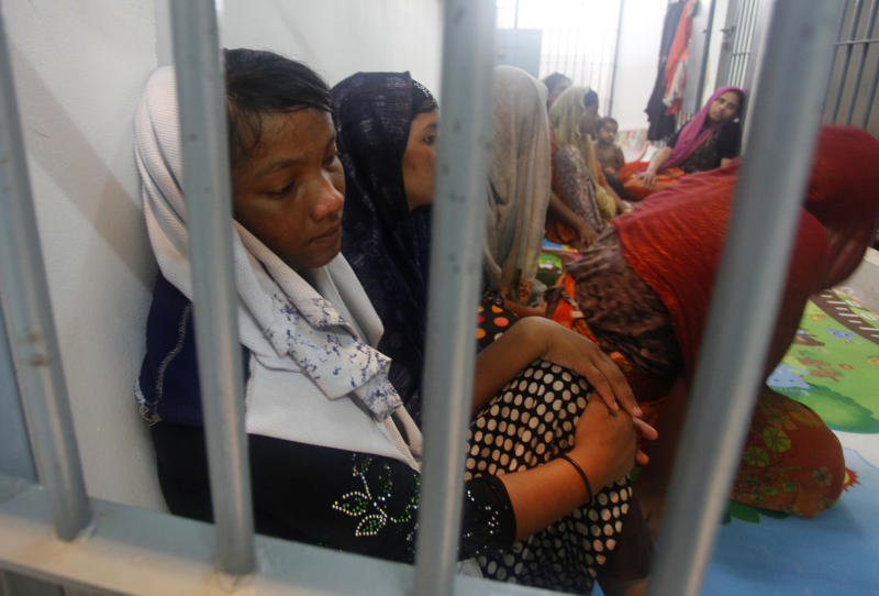 FILE- In this June 12, 2019, file photo, Rohingya refugees sit behind bars at a police station in Satun province, southern Thailand after Thai officials say they have discovered 65 ethnic Rohingya Muslim refugees who were shipwrecked and stranded in southern Thailand. A U.N. report says organized crime syndicates in Southeast Asia are flourishing in the illegal trafficking of drugs, wildlife, counterfeit goods and people.(AP Photo/Sumeth Panpetch, File)