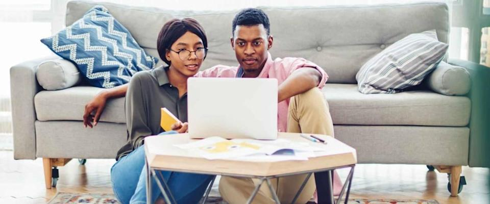 Dark skinned couple in love looking at mortgage rates on a laptop computer while sitting on their living room floor.