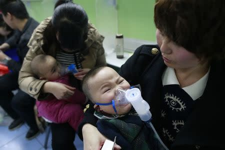 File photo shows children with respiratory illness receiving treatment at a hospital in Beijing