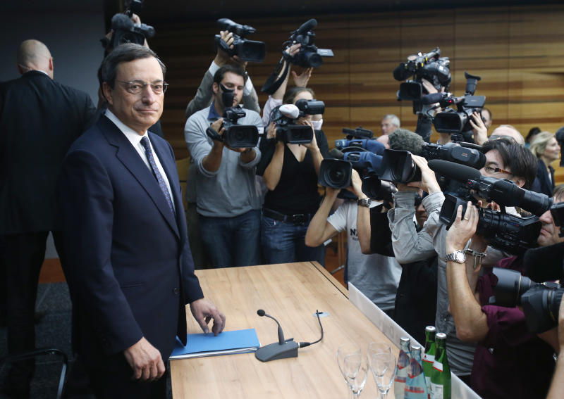 President of European Central Bank Mario Draghi is surrounded by media people at the beginning of a news conference in Frankfurt, Germany, Thursday, Sept. 6, 2012, following a meeting of the ECB governing council concerning the further strategies in the European financial crisis. (AP Photo/Michael Probst)