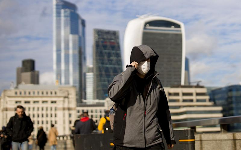 A man wearing a protective face mask, walks across London Bridge  - TOLGA AKMEN /AFP
