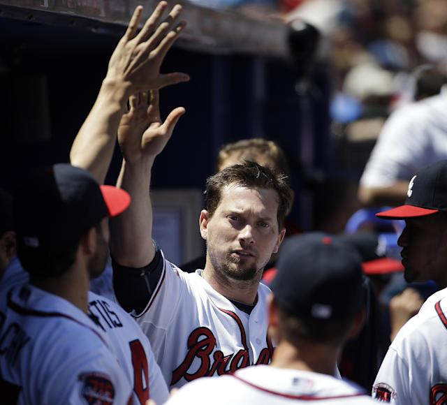 Atlanta Braves' Chris Johnson, center, high-fives teammates after scoring off a single by Ryan Doumit in the fourth inning of a baseball game against the Miami Marlins, Wednesday, April 23, 2014, in Atlanta. (AP Photo/David Goldman)
