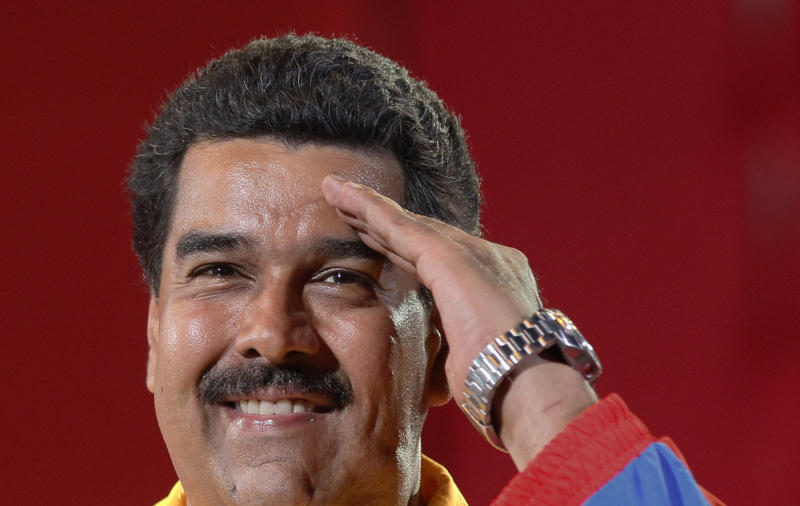 Venezuela's interim President Nicolas Maduro does a military salute to supporters during a campaign rally in Valencia. Venezuela, Thursday, April 4, 2013. The presidential election to replace Venezuela's late President Hugo Chavez is scheduled for April 14. (AP Photo/Ariana Cubillos)