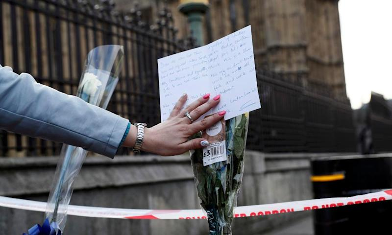 A woman reads a card on a floral tribute at the Houses of Parliament on Thursday