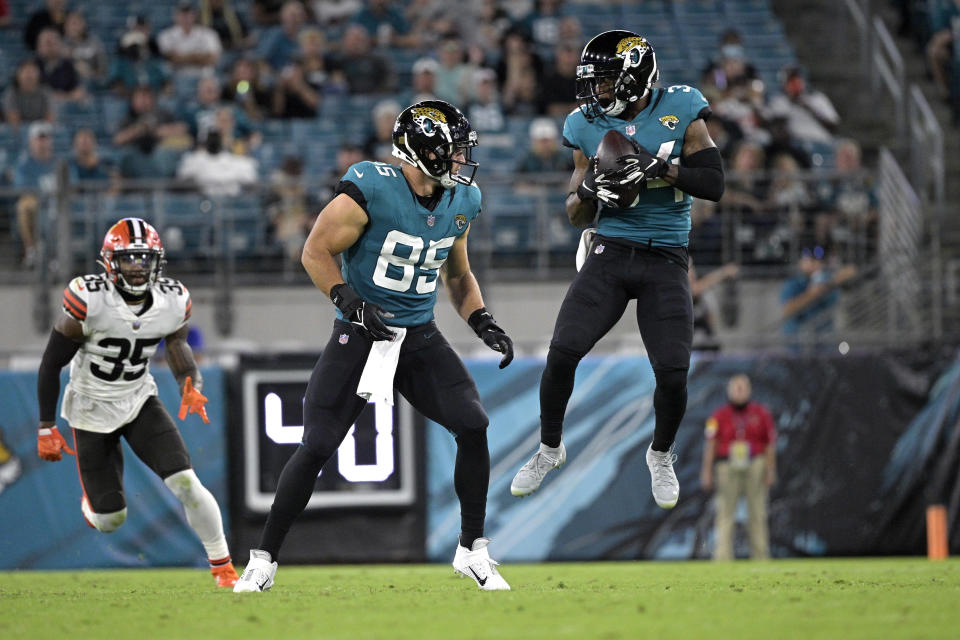 Jacksonville Jaguars wide receiver Tavon Austin, right, makes a reception as tight end Tim Tebow (85) looks to block oncoming Cleveland Browns safety Jovante Moffatt (35) during the first half of an NFL preseason football game, Saturday, Aug. 14, 2021, in Jacksonville, Fla. (AP Photo/Phelan M. Ebenhack)