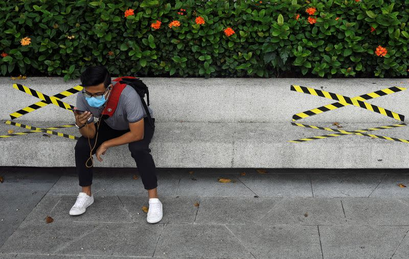 Man sits on a bench with distance markers along Marina Bay in Singapore