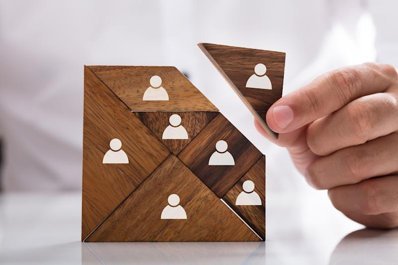 Human resources concept: A man solves a wooden tangram puzzle with blocks which are painted with icons for humans.