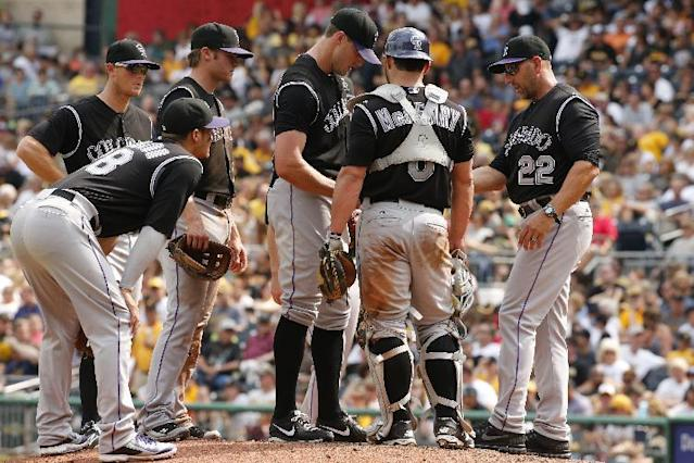 Colorado Rockies manager Walt Weiss (22) takes the ball from relief pitcher Matt Belisle, center, during the seventh inning of a baseball game against the Pittsburgh Pirates in Pittsburgh Sunday, July 20, 2014. The Pirates won 5-3. (AP Photo/Gene J. Puskar)