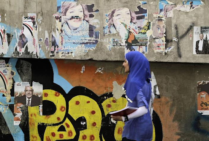 An Egyptian woman passes by a wall with defaced posters of presidential candidates in Cairo, Egypt, Monday, May, 21, 2012. The May 23-24 presidential election is the first since last year's ouster of longtime authoritarian ruler Hosni Mubarak (AP Photo/Hasan Jamali)