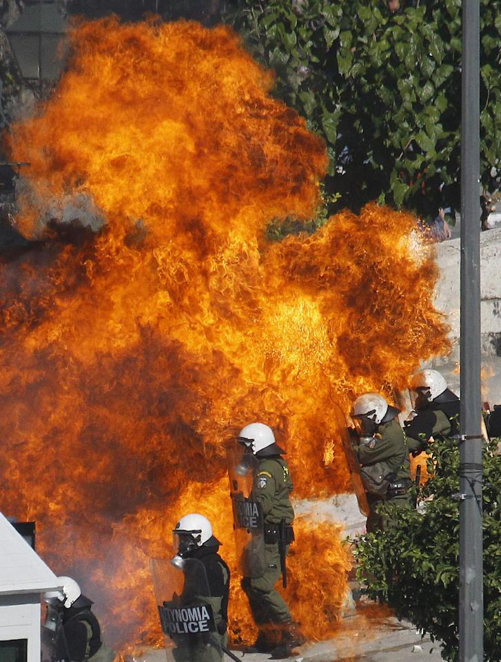 A fire bomb explodes next to riot police during clashes outside the Greek Parliament on Wednesday Oct. 19, 2011. A two-day general strike that unions vow will be the largest in years grounded flights, disrupted public transport and shut down everything from shops to schools in Greece on Wednesday, as at least 50,000 protesters converged in central Athens. All sectors, from dentists, state hospital doctors and lawyers to shop owners, tax office workers, pharmacists, teachers and dock workers walked off the job ahead of a Parliamentary vote Thursday on new austerity measures. (AP Photo/Dimitri Messinis)