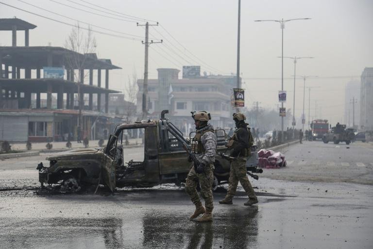 A photo taken on December 20, 2020 shows members of the Afghan security forces at the site of an attack in Kabul. Talks to end Afghanistan's long running war have been marred by an increase in violence from the start
