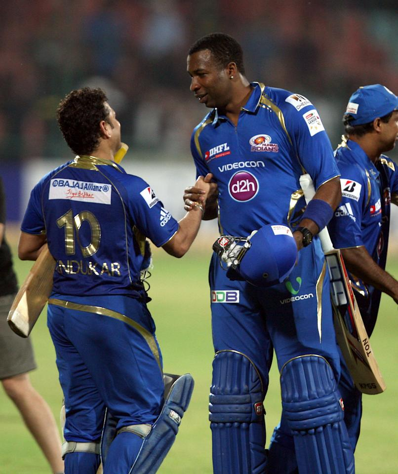 MI batsman Kieron Pollard celebrates with Sachin Tendulkar after wining the 2nd CLT20 semi-final match between Mumbai Indians and Trinidad & Tobago at Feroz Shah Kotla, Delhi on Oct. 5, 2013. (Photo: IANS)