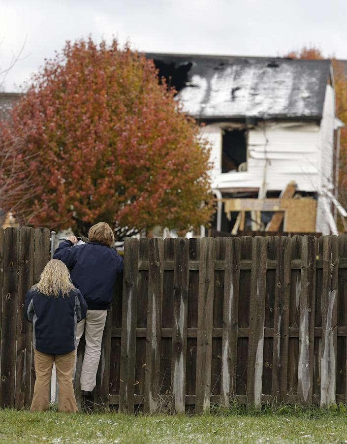 Onlookers try to view the damage that destroyed two homes and made dozens more uninhabitable, Monday, Nov. 12, 2012, in Indianapolis. The explosion killed two people. (AP Photo/Darron Cummings)