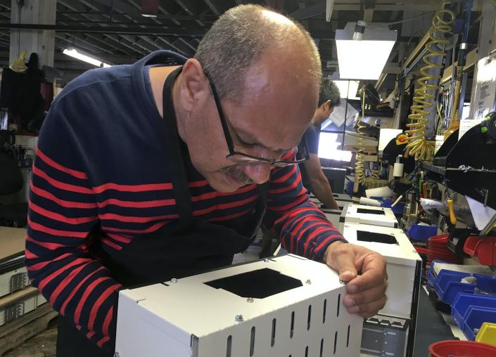 """<span class=""""caption"""">Former Iraqi refugee Majid Al Lessa works on a lighting fixture on the assembly floor of LiteLab, a factory that employs refugees in Buffalo, N.Y.</span> <span class=""""attribution""""><a class=""""link rapid-noclick-resp"""" href=""""http://www.apimages.com/metadata/Index/Trump-Fewer-Refugees/82f3346b282449d99e067ebe55913774/5/0"""" rel=""""nofollow noopener"""" target=""""_blank"""" data-ylk=""""slk:AP Photo/ Michael Hill"""">AP Photo/ Michael Hill</a></span>"""