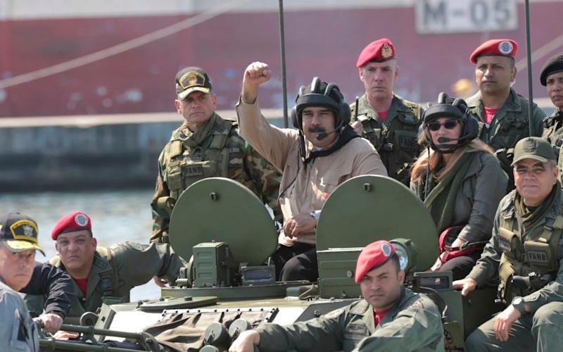 Venezuelan President Nicolas Maduro raises his fist from an amphibious tank as he poses for photos alongside military officers this weekend - Miraflores presidential palace press office via AP