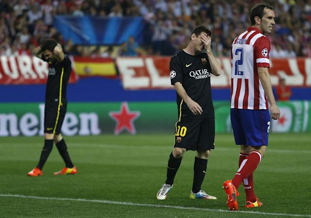 Barcelona's Lionel Messi and Cesc Fabregas react next to Atletico's Diego Godin, right, during the Champions League quarterfinal second leg soccer match between Atletico Madrid and FC Barcelona at the Vicente Calderon stadium in Madrid, Spain, Wednesday, April 9, 2014. (AP Photo/Andres Kudacki)