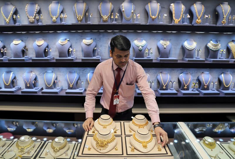 FILE PHOTO: A salesman displays gold necklaces and earrings inside a jewellery showroom in Mumbai, India
