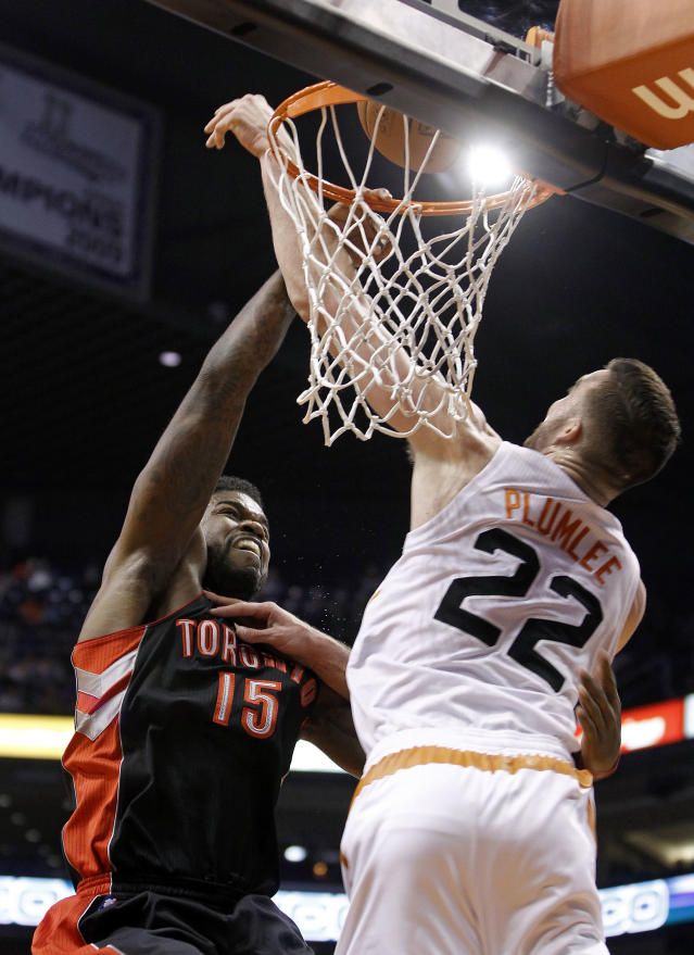 Toronto Raptors' Amir Johnson (15) has his shot blocked by Phoenix Suns' Miles Plumlee (22) during the first half of an NBA basketball game on Friday, Dec. 6, 2013, in Phoenix. (AP Photo/Ralph Freso)