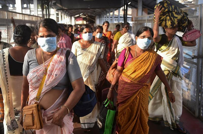 Indian women wear masks as a precaution against coronavirus as they leave the Attukal temple in Thiruvananthapuram, Kerala: AP