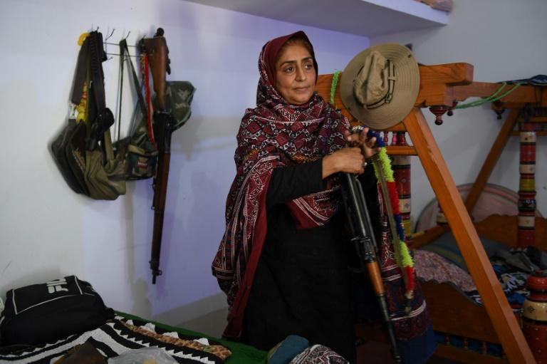 Pakistani woman Mukhtiar Naz, known as Waderi Nazo Dharejo, holds a gun at her ancestral home in Qazi Ahmed in Sindh province