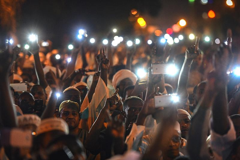 Supporters of Sudanese Islamist movements hold up their phones as they chant slogans during a rally in front of the presidential palace in downtown Khartoum (AFP Photo/MOHAMED EL-SHAHED                   )