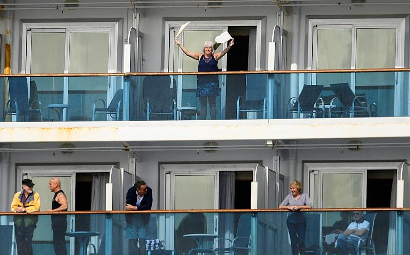 7 A passenger waves aboard the Grand Princess off the coast of San Francisco as a media boat approaches on Sunday, March 8, 2020