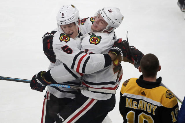Chicago Blackhawks center Jonathan Toews, right, celebrates his game-winning goal with defenseman Connor Murphy (5) as a young Boston Bruins fan watches in the overtime period of an NHL hockey game, Thursday, Dec. 5, 2019, in Boston. The Blackhawks beat the Bruins 4-3 in overtime. (AP Photo/Elise Amendola)