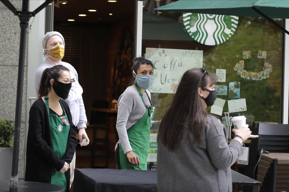 In this May 6, 2020 photo, employees at a Starbucks Coffee store that is open for mobile orders wear masks as they watch a customer leave with an order in downtown Seattle. Nearly all retail stores and restaurants in the area are currently closed or operating under reduced levels of service due to the outbreak of the coronavirus and state-wide stay-at-home orders, which has led to thousands of workers losing their jobs or being furloughed. (AP Photo/Ted S. Warren)