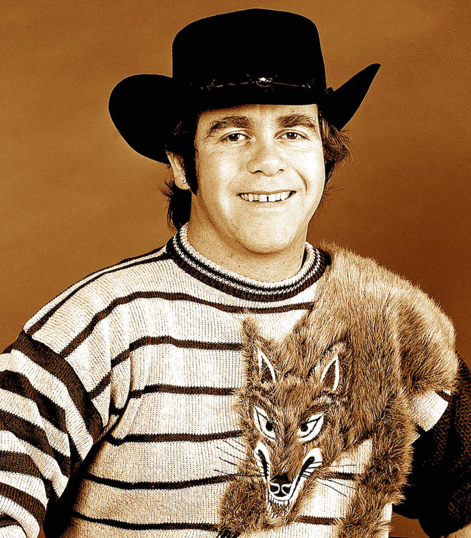 <p>Elton John in a casual striped sweater with a fox crawling over his shoulder. He topped it off with a black cowboy hat in this 1984 portrait. (Photo: Getty Images) </p>