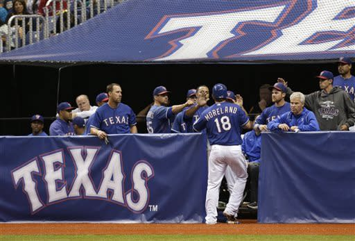 Texas Rangers' Mitch Moreland (18) celebrates with teammates after he scored during the sixth inning of an exhibition baseball game against the San Diego Padres, Friday, March 29, 2013, in San Antonio. Texas won 5-4. (AP Photo/Eric Gay)