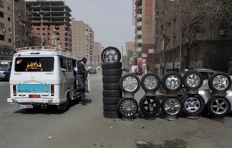 In this Monday, March 12, 2012 photo, a public transportation minibus unloads a passenger in the middle of the road while tires displayed for sale encroach on a street in Cairo, Egypt. The streets and sidewalks of Cairo have always been rather chaotic. But they've only gotten worse in the political turmoil as Egypt stumbles towards a new system following the fall of President Hosni Mubarak. (AP Photo/Nasser Nasser)