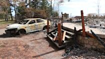 The remains of a cottage and the burnt shell of a decommissioned RCMP cruiser are seen at a property in Portapique, N.S., that belonged to the gunman who killed 22 people on April 18 and 19. (Steve Lawrence/CBC)