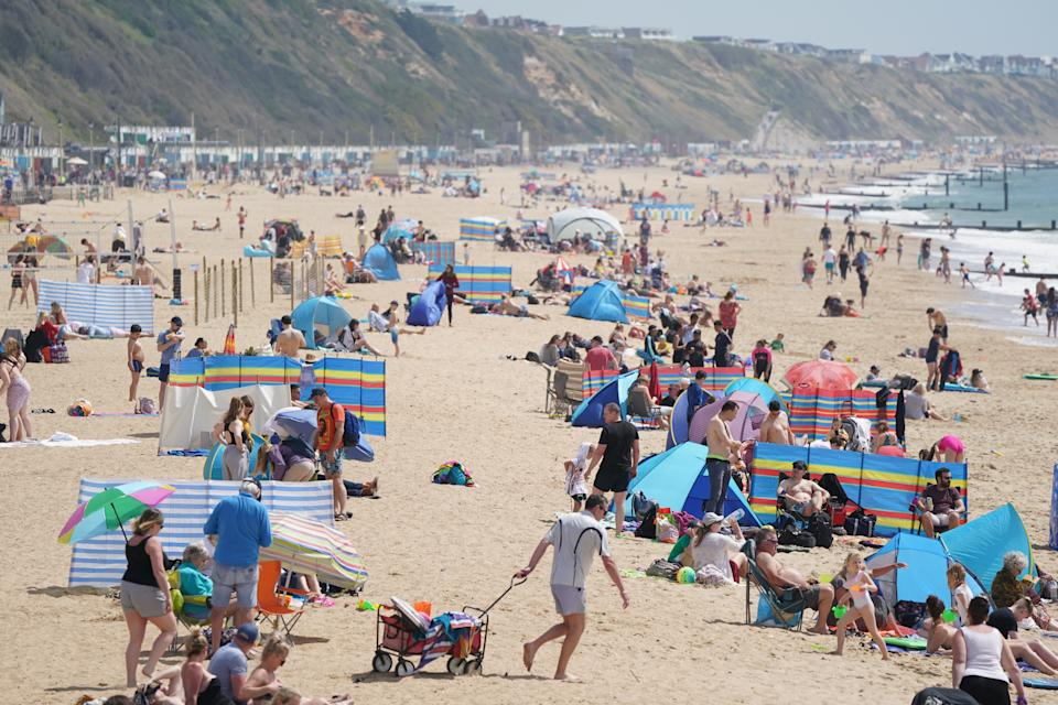 People on Boscombe beach, with the bank holiday weekend expected to bring blue skies and widespread sunshine. Picture date: Sunday May 30, 2021.