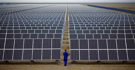 File photo of worker inspecting solar panels at a solar farm in Dunhuang