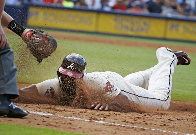 Atlanta Braves' Jason Heyward is tagged out as his tries to get back to first base after being caught in a rundown in the third inning of a baseball game against the Arizona Diamondbacks in Atlanta, Saturday, July 5, 2014. (AP Photo/John Bazemore)